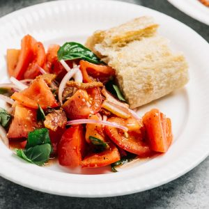Tomato salad with bacon dressing on a white plate with a slice of crusty bread for dipping.