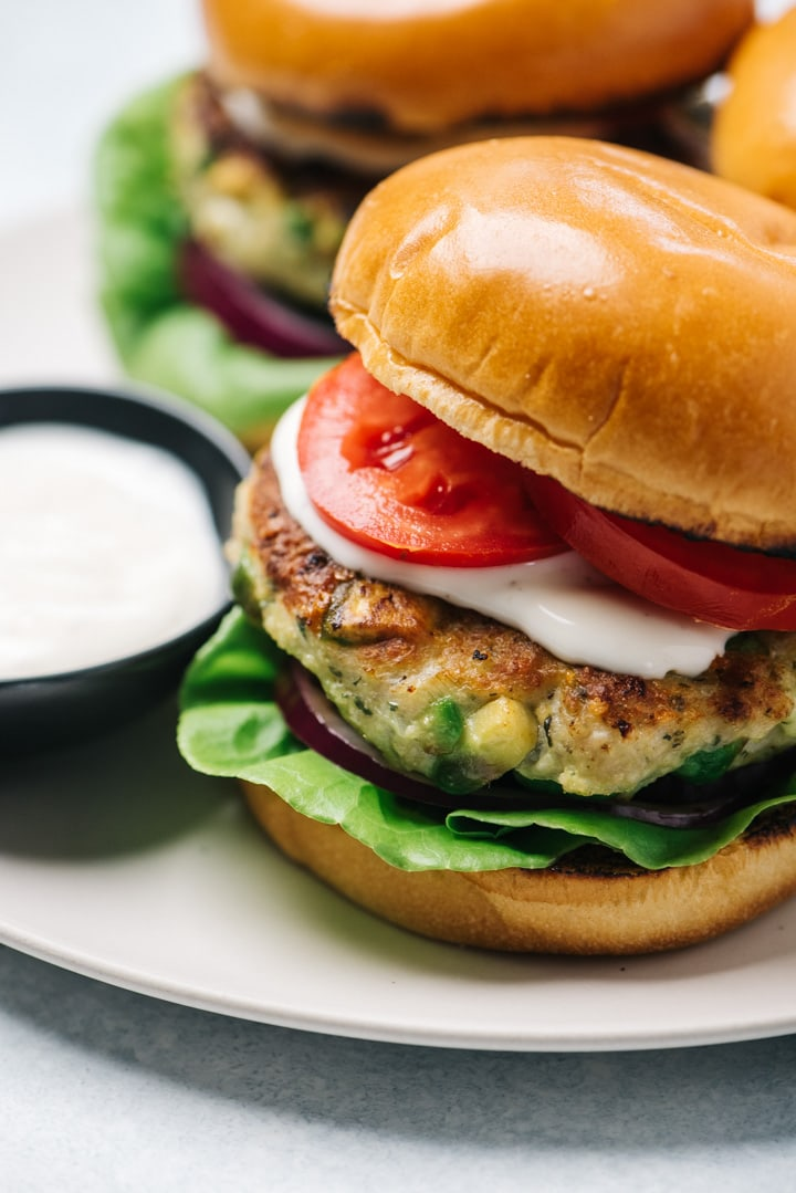 Side view, an avocado ranch chicken burger on a brioche bun with lettuce, tomato, and onion.
