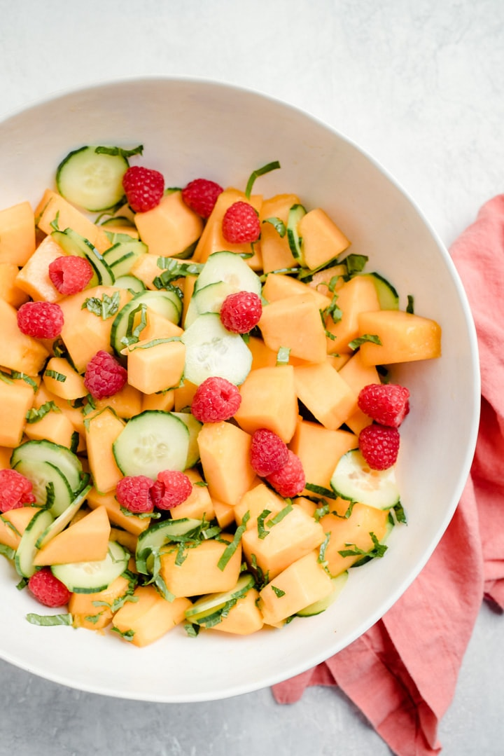 A large serving bowl of cantaloupe melon salad with cucumbers, raspberries, fresh herbs, and a lemon honey dressing.