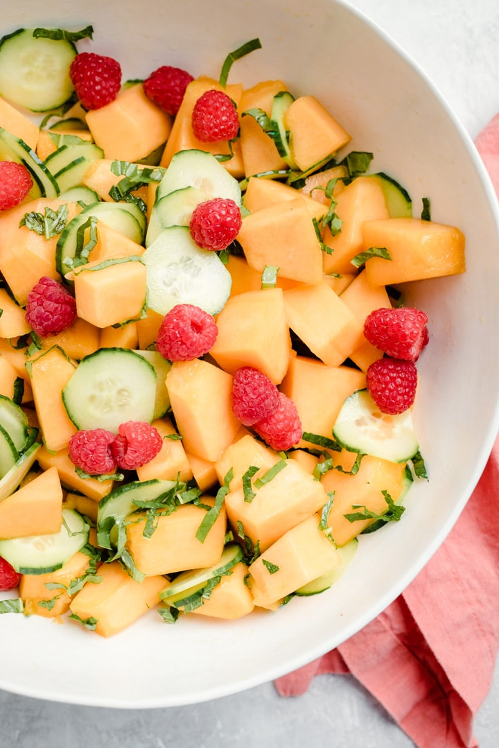 Cantaloupe salad in a white serving bowl with a salmon colored linen napkin on a white table.