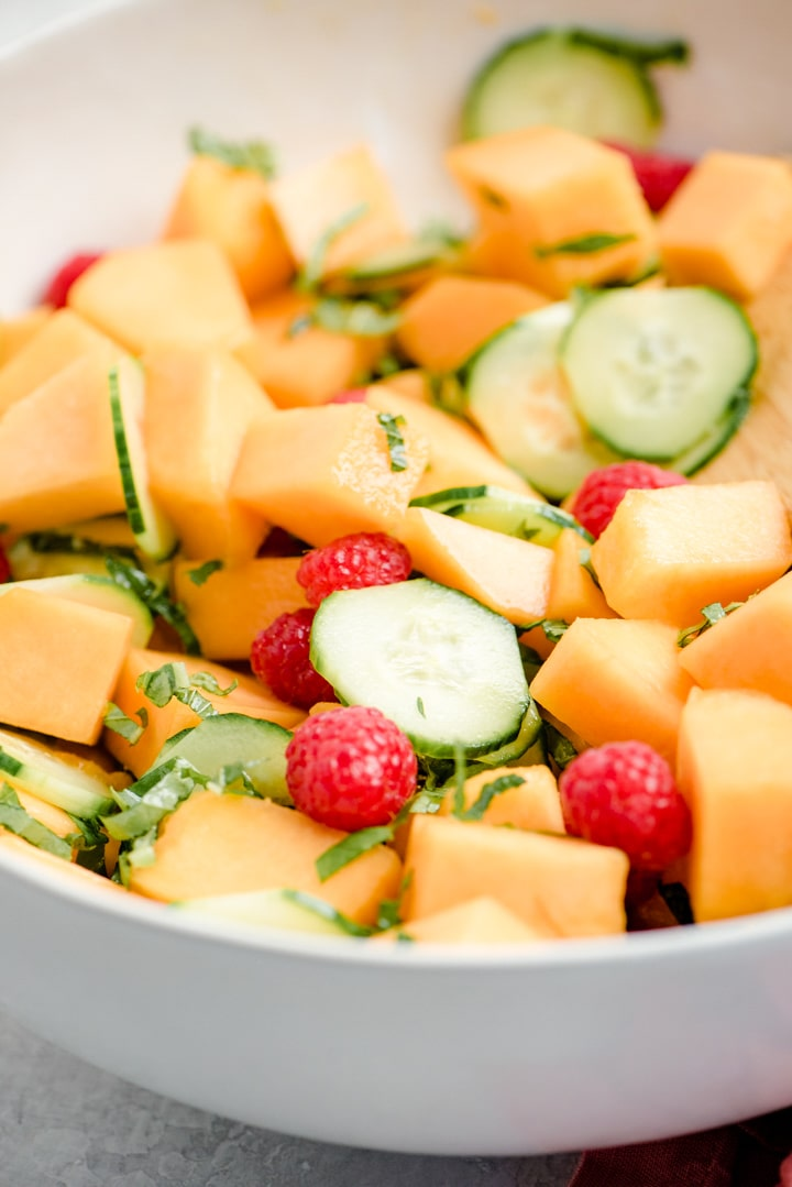 Side view, a large serving bowl of cantaloupe salad with cucumbers, raspberries, mint, and honey lemon dressing.
