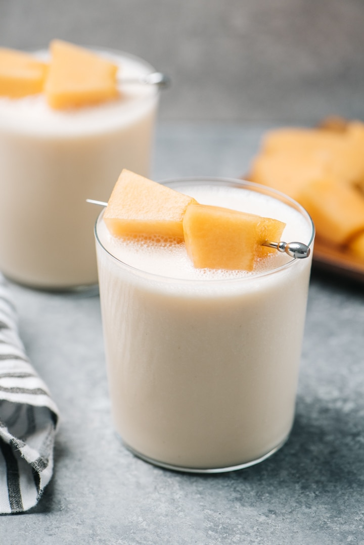 Side view, two cantaloupe smoothies garnished with fresh fruit on a cement background.