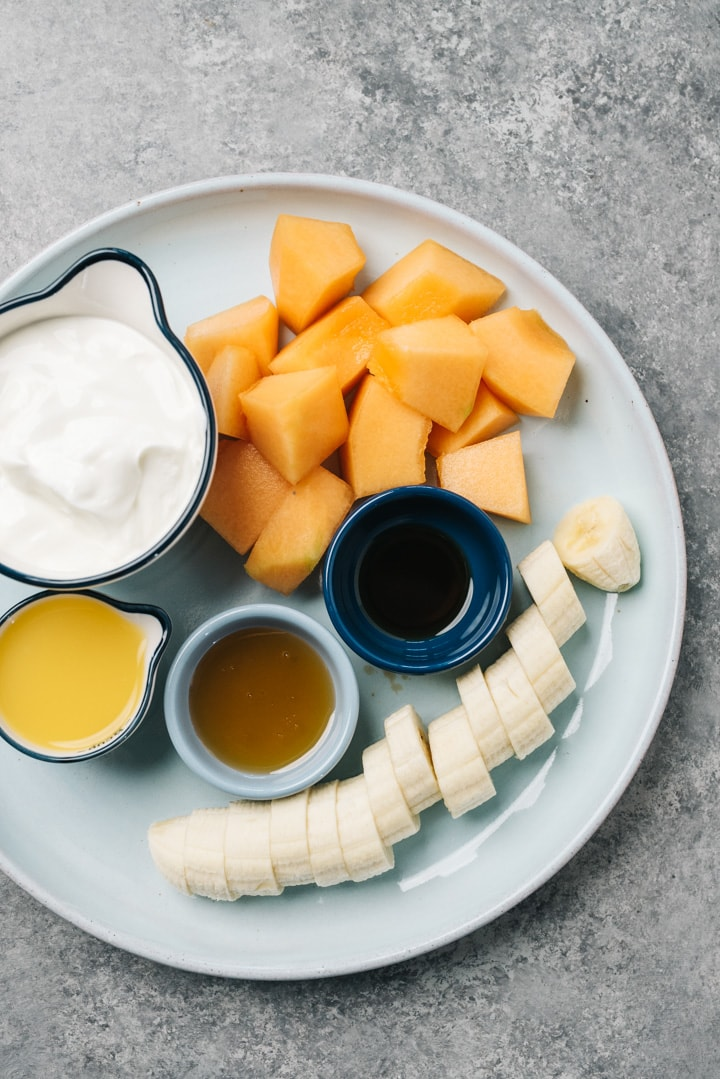 The ingredients for a smoothie made with fresh cantaloupe arranged on a blue plate.