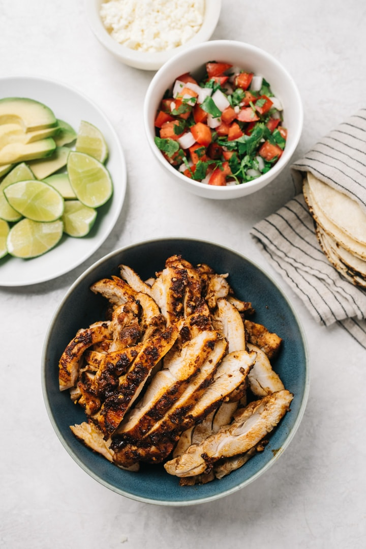 A blue bowl of sliced grilled taco chicken surrounded by bowls of garnishes and a stack of corn torillas.
