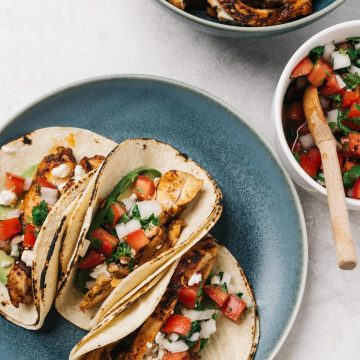 Three chicken street style tacos on a blue plate surrounded by bowls of garnishes and a bowl of cooked chicken slices.
