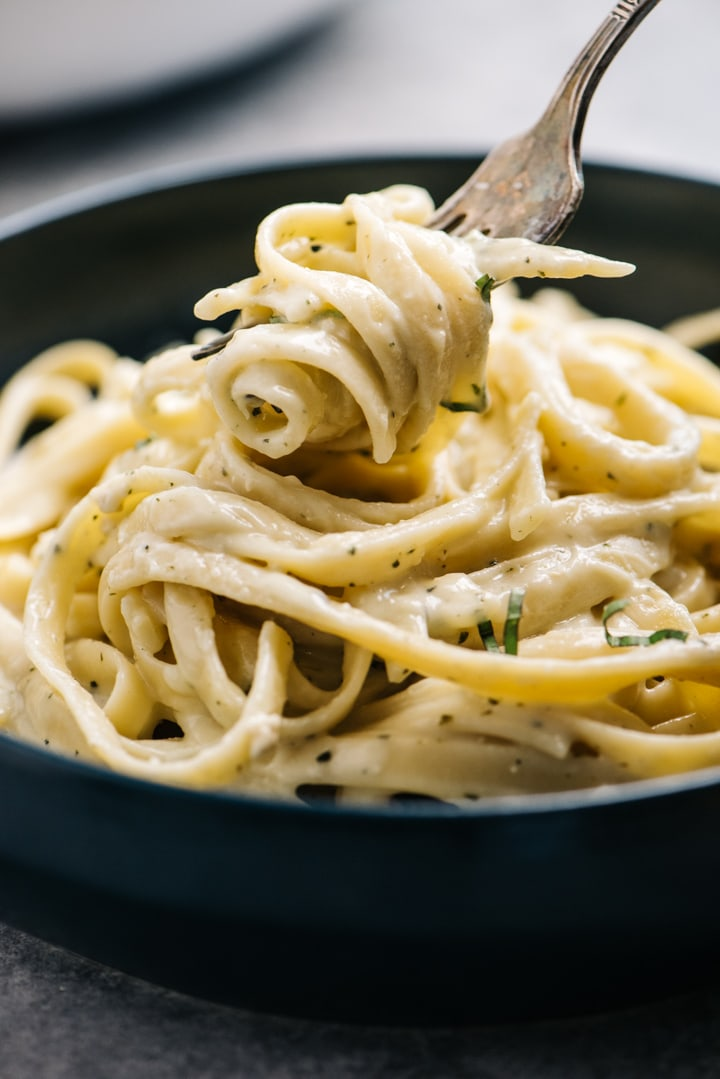 Side view, fettuccine tossed with creamy pesto sauce wound around a fork.