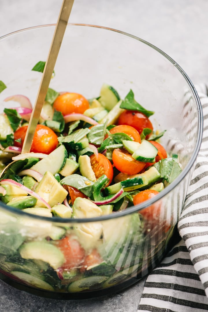 Cucumber, tomato, and avocado salad in a glass bowl with a striped linen.