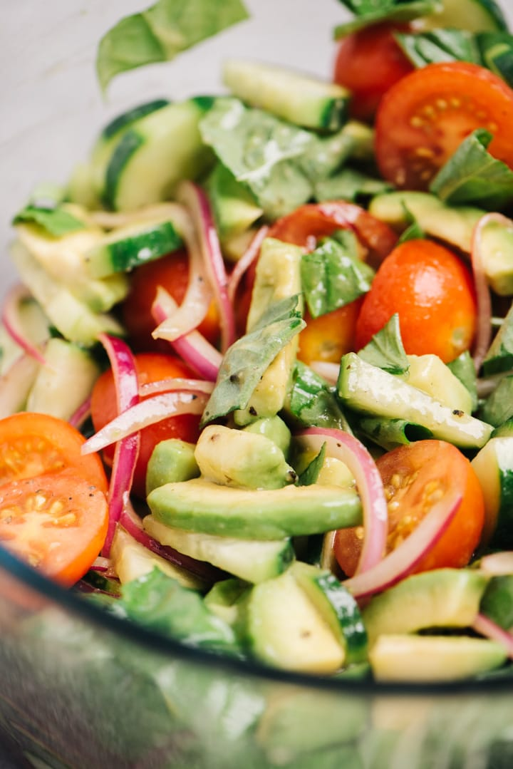 Side view, looking into a glass salad bowl filled with cucumber, tomato, and avocado salad with red onions and balsamic dressing.