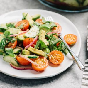 Side view, a serving of cucumber, tomato, and avocado salad on a white plate with a large serving bowl in the background.