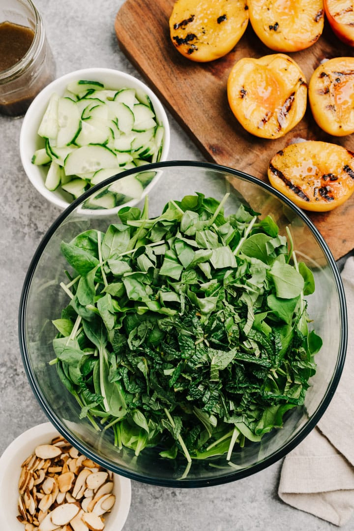 Salad greens with basil and mint in a glass bowl surrounded with grilled peaches, cucumbers, toasted almonds, and balsamic vinegar.