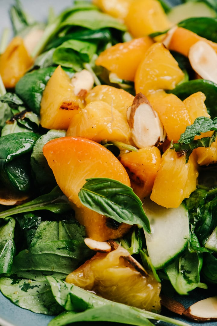 Detail of diced grilled peaches served over mixed greens with basil, mint, cucumbers, toasted almonds, and balsamic dressing.