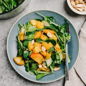 A plate of grilled peach salad on a cement table with a bowl of mixed greens, a bowl of diced grilled peaches, and a small pinch bowl of toasted almonds.