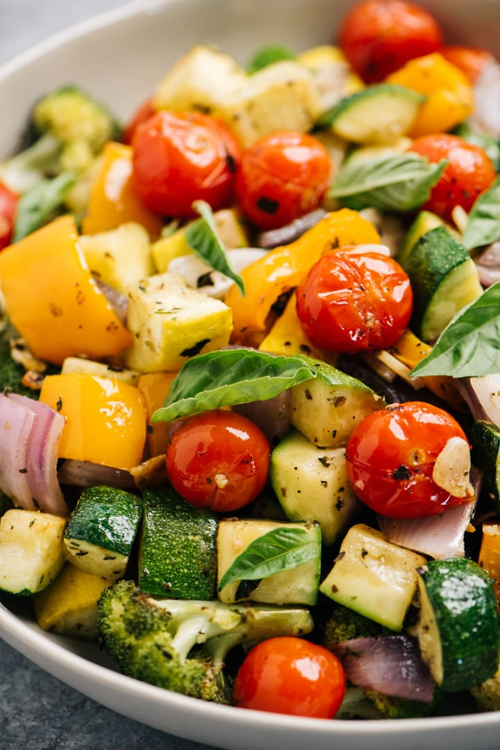 Side view, sheet pan roasted vegetables in a serving bowl garnished with fresh basil leaves.
