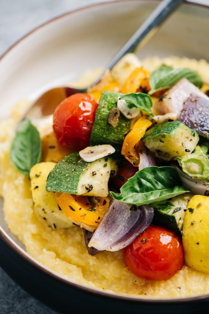 Side view, roasted vegetables served over polenta, garnished with fresh basil leaves.
