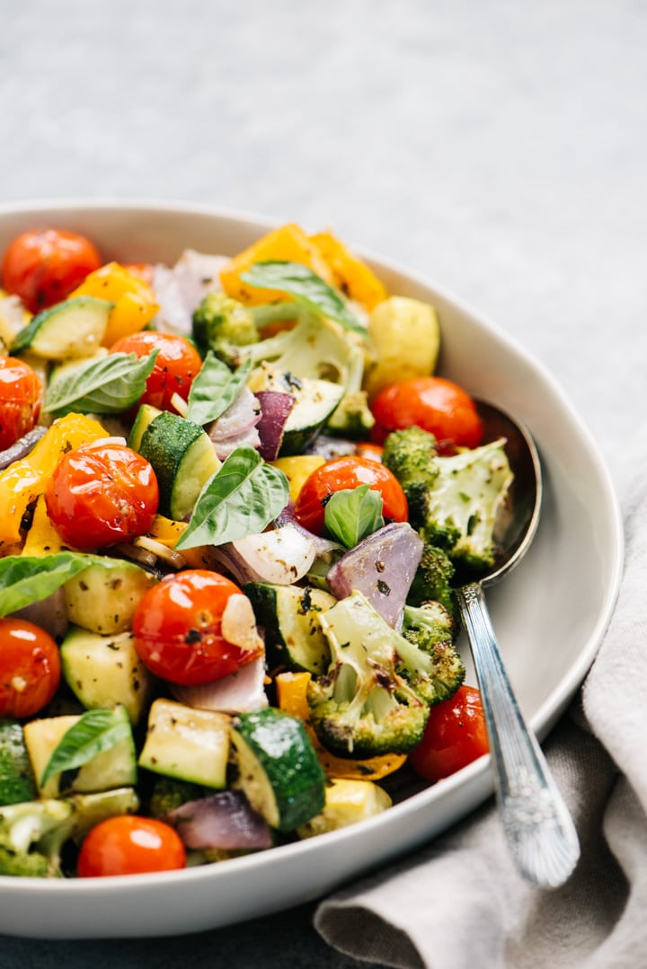 Side view, a bowl of roasted summer vegetables in a tan serving bowl with a silver serving spoon.