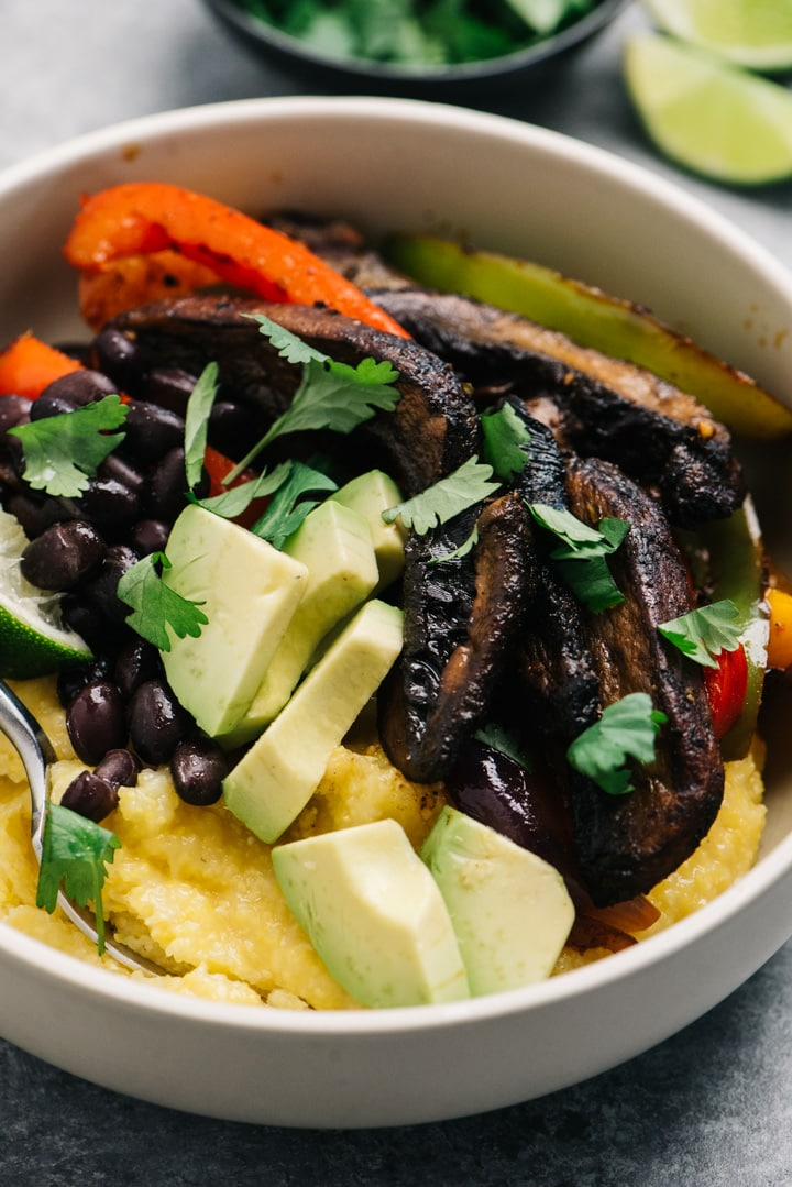 Vegan portobello fajita bowl with bell peppers and onions served over dairy free polenta, served with diced avocado.