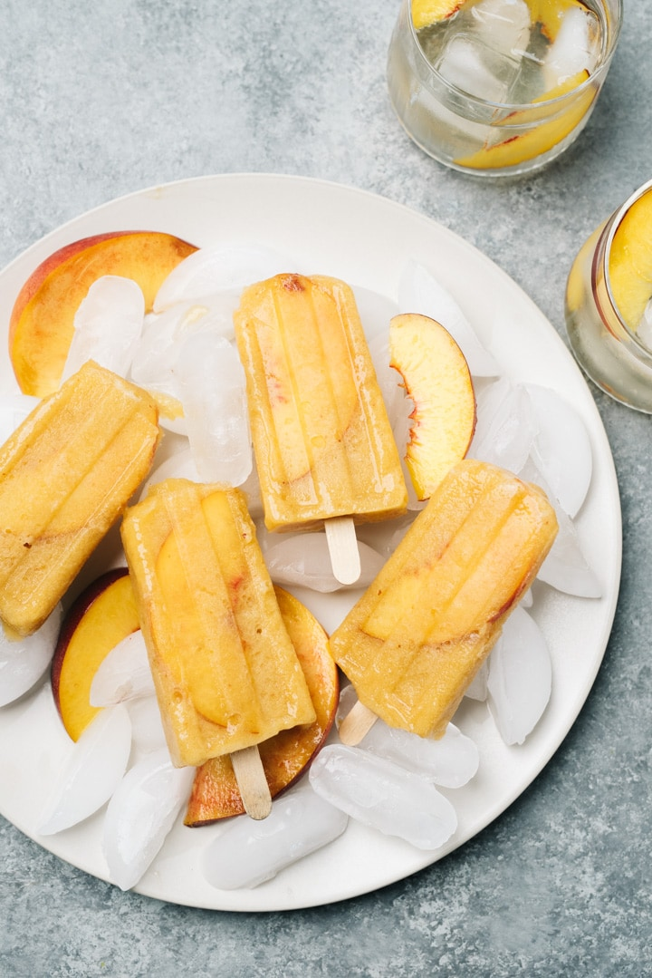 White sangria popsicles on a plate with ice and fresh peach slices on a cement table with two white sangria popsicles.