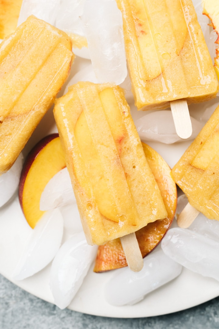 Boozy popsicles on a plate with ice and slices of fresh peaches and nectarines.