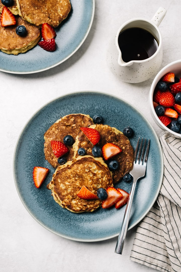 Two blue plates with oatmeal pancakes on a cement table with a small pitcher of maple syrup and a bowl of fresh sliced berries.