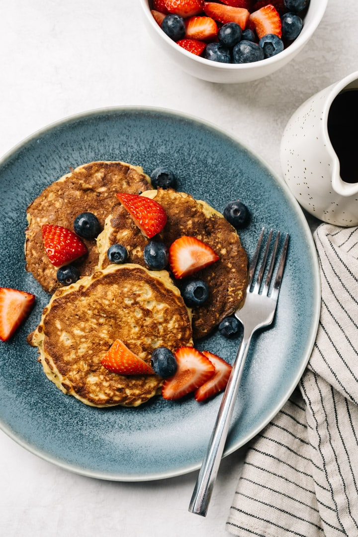 Oatmeal pancakes on a blue plate topped with fresh berries with a small pitcher of maple syrup on a cement tabletop.