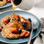 A woman's hand pouring maple syrup onto three banana oatmeal pancakes topped with fresh berries.