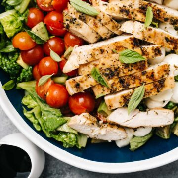 A large serving bowl of caprese salad topped with grilled chicken and a small pitcher of balsamic reduction dressing.