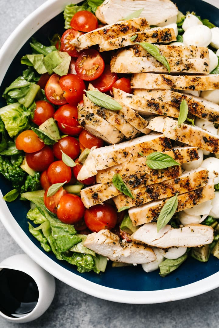 A large serving bowl of chicken caprese salad with romaine lettuce, fresh basil, and grilled chicken.