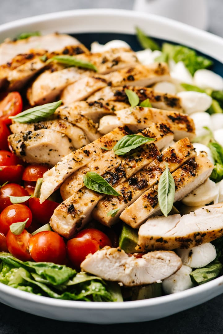 Side view, a large salad bowl with romaine lettuce, tomatoes, mozzarella, avocado, and sliced grilled chicken topped with basil leaves.