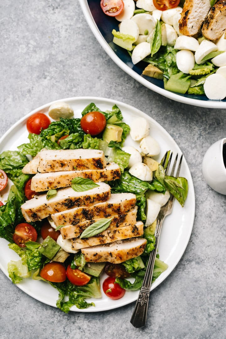 A single serving of grilled chicken caprese salad on a white plate with a small pitcher of balsamic reduction dressing.