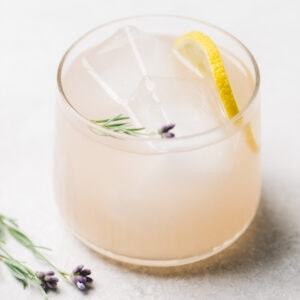 A lavender cocktail with gin, lemon juice, and lavender simple syrup on a cement background.