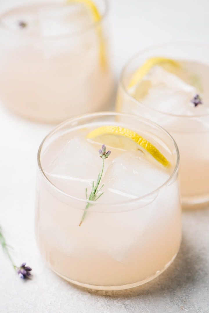 Three lavender gin sour cocktails on a cement background garnished with lemon slices and fresh lavender flowers.
