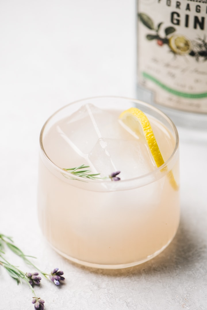 A gin sour lavender cocktail on a cement background with a bottle of McClintock Forager Gin in the background.