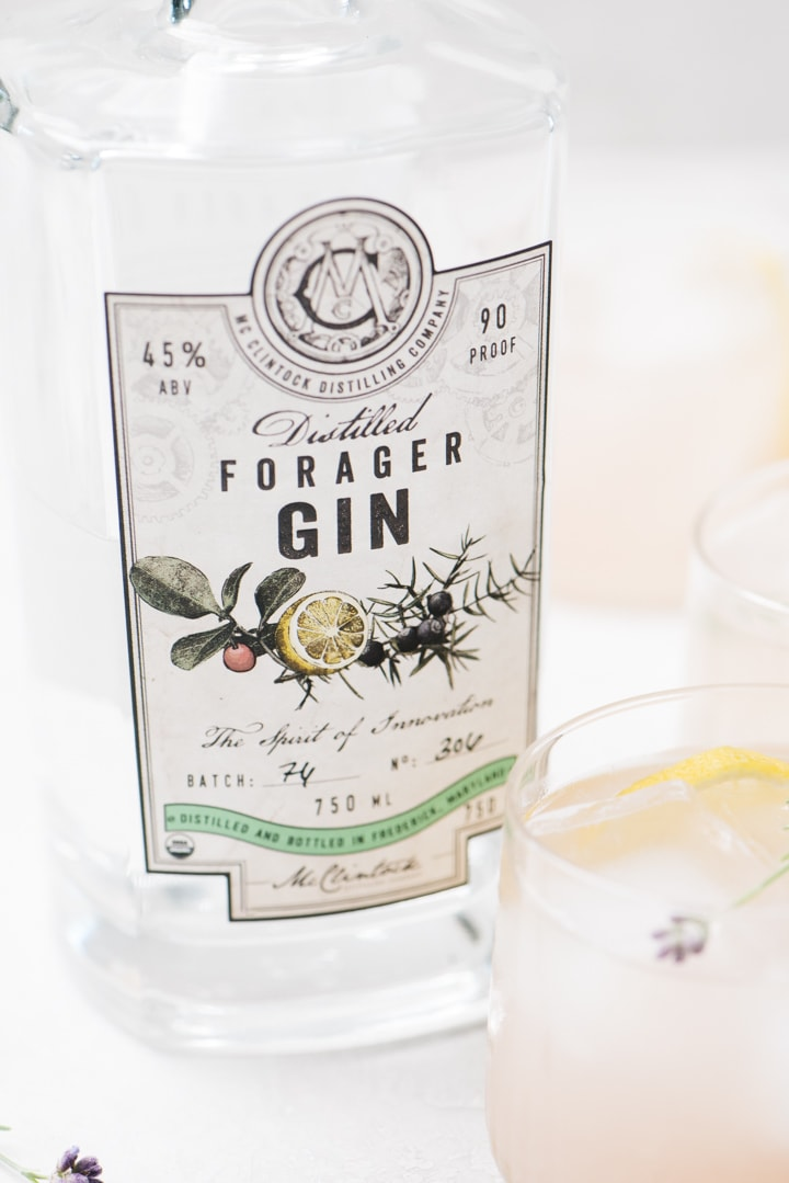 A bottle of McClintock Forager gin surrounded by lavender cocktails on a cement background.
