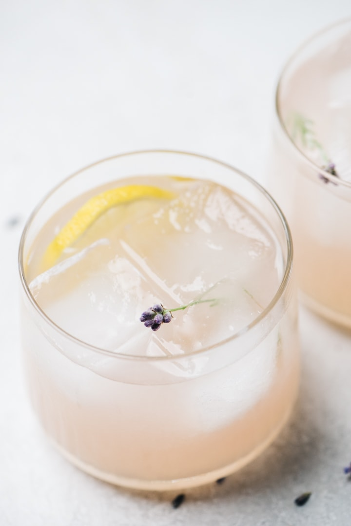 Two gin lavender cocktails on a cement background garnished with lemon wheels and fresh lavender stems.
