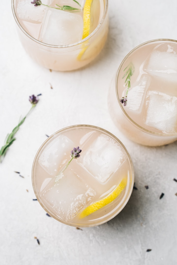 Overhead, three lavender gin sour cocktails on a cement background garnished with fresh lavender flowers.