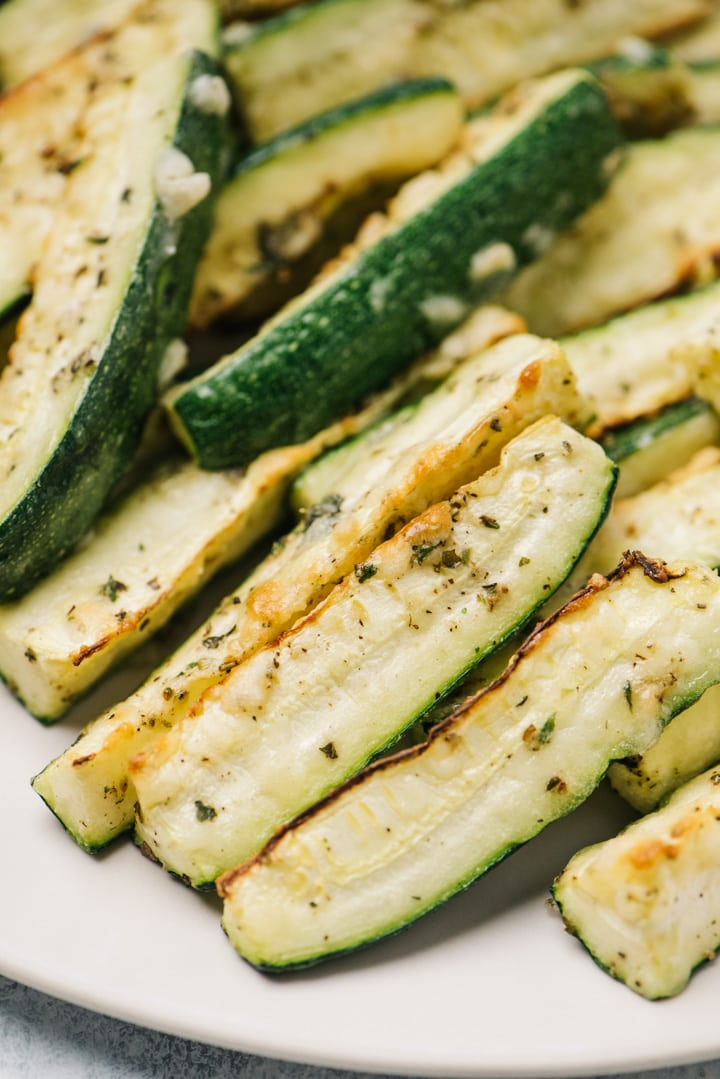 Side view, a stack of parmesan roasted zucchini wedges on a cream colored plate.