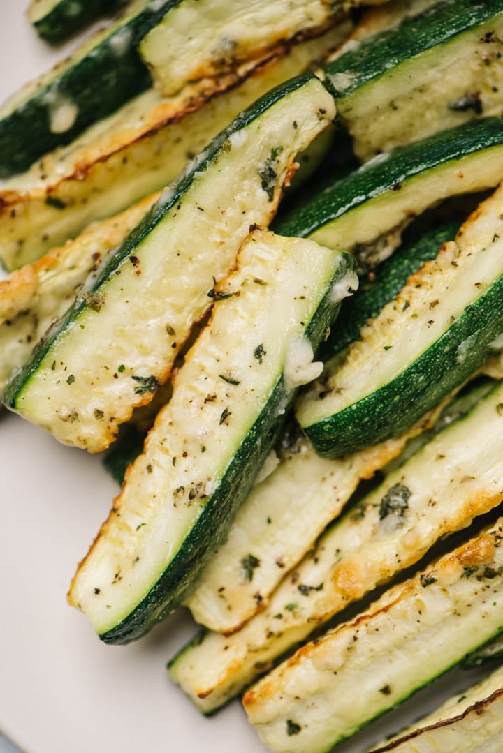 Side view, a stack of roasted zucchini fries on a cream colored plate.