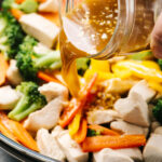 Side view, pouring stir fry sauce into a skillet with chicken and vegetables.