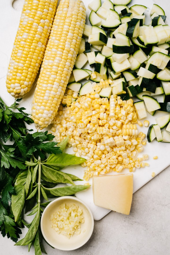 The ingredients for sauteed zucchini and corn arranged on a white cutting board on a concrete background.