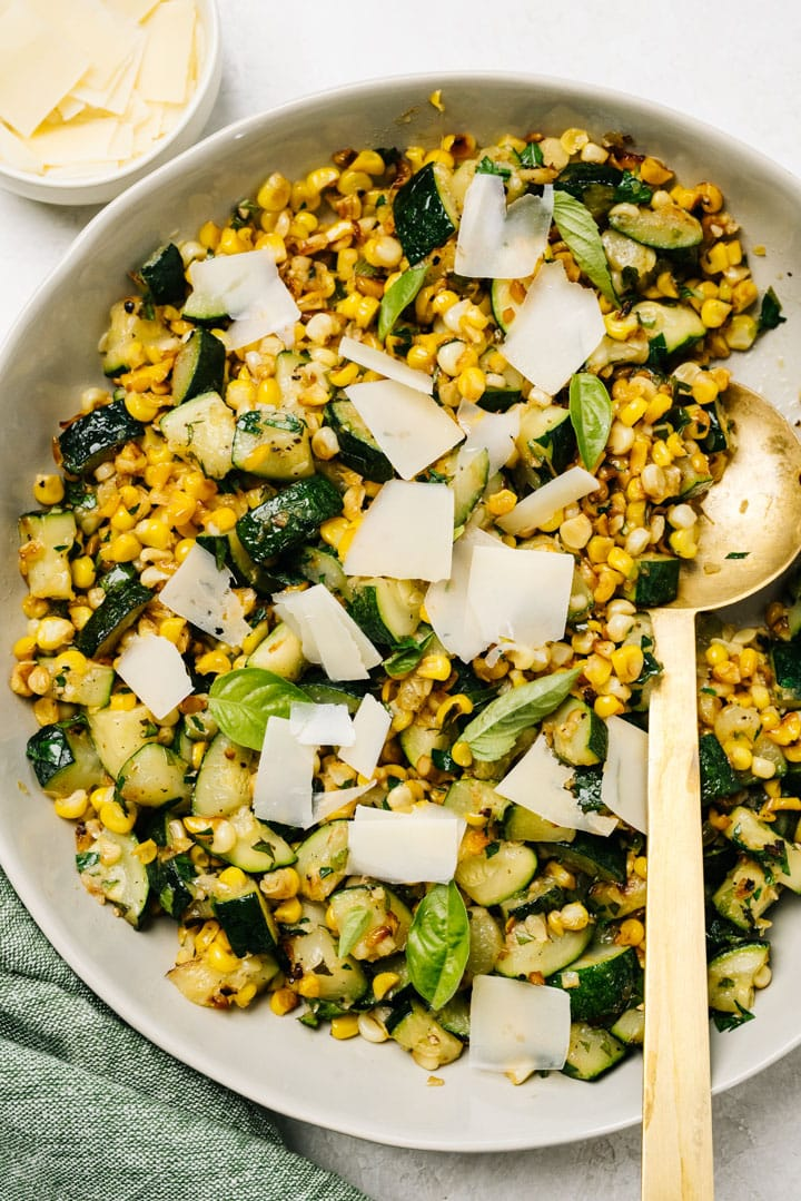 A serving bowl of sauteed zucchini and corn garnished with shaved parmesan and fresh basil.