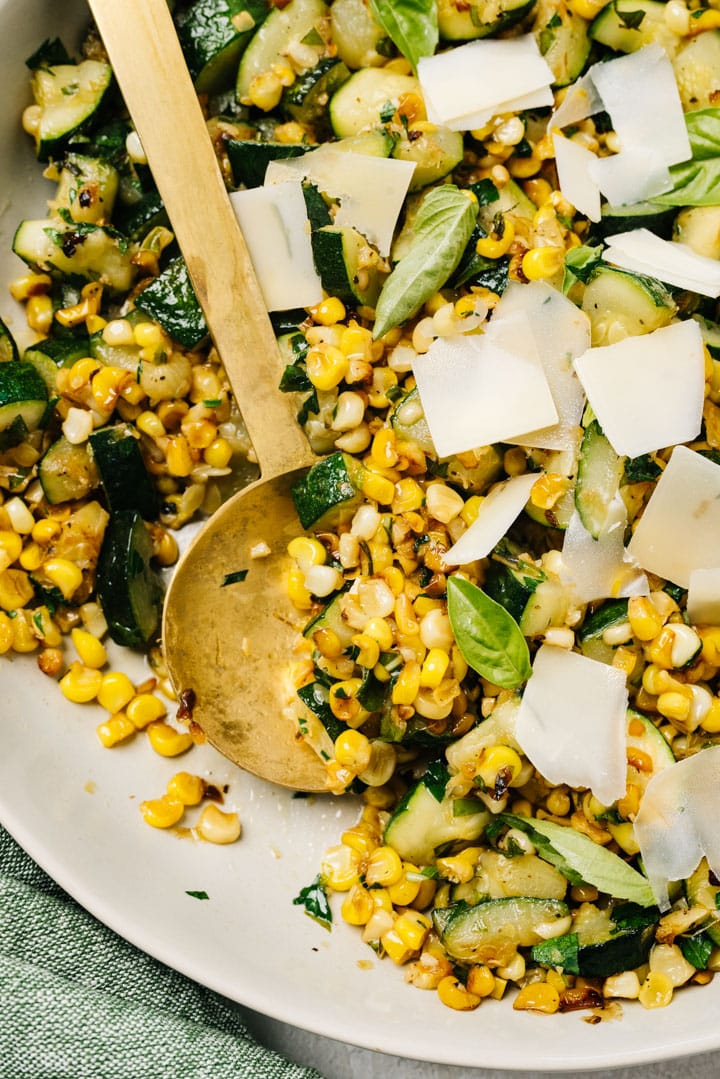A gold serving spoon in a serving bowl of zucchini and corn with parmesan and basil.