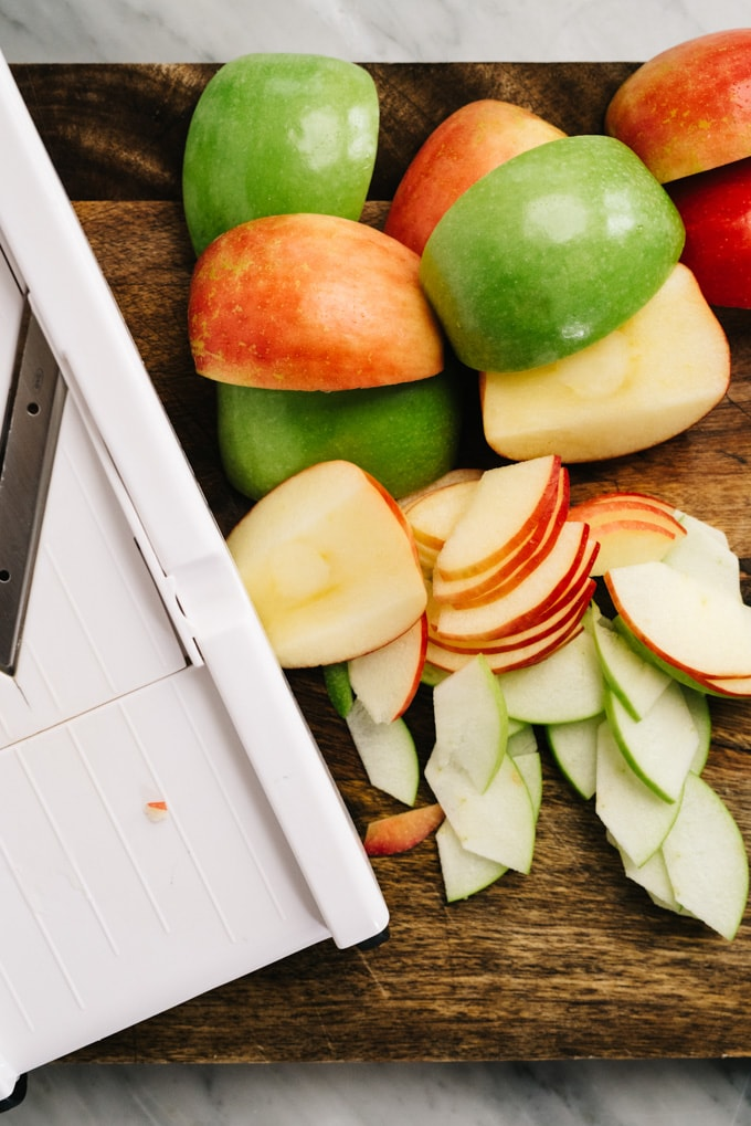 A mandoline, apple chunks, and thinly sliced apples on a cutting board.