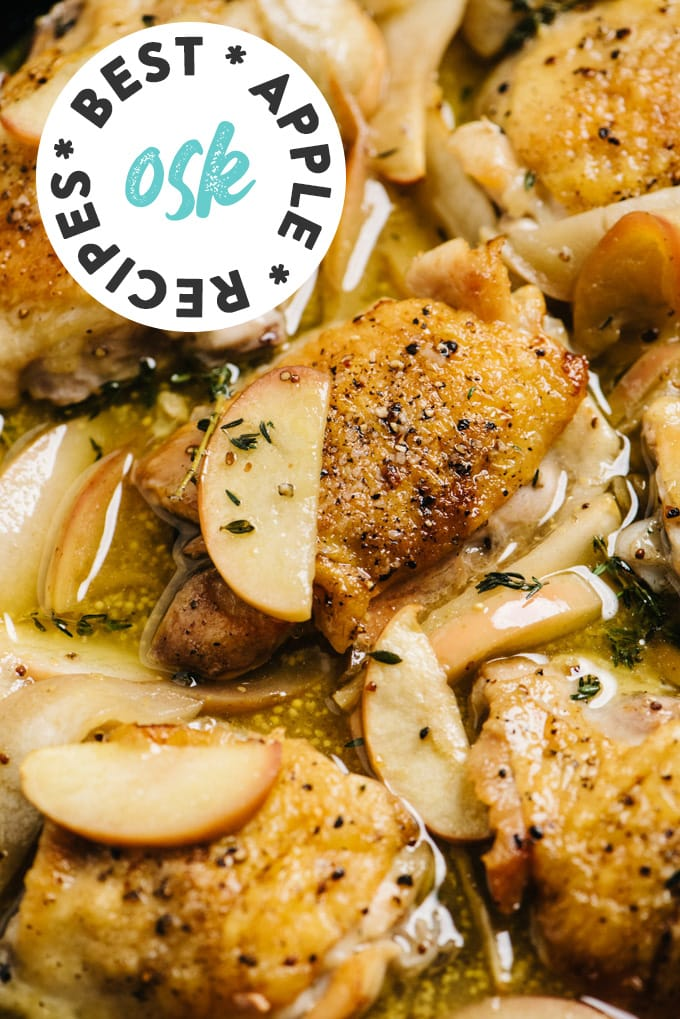 Crispy chicken thighs with apples and cider sauce in a cast iron skillet.