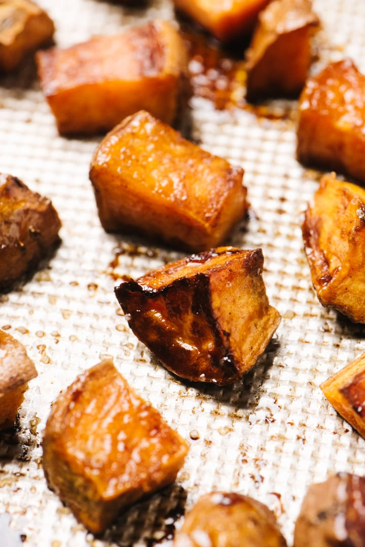 Side view, roasted sweet potato cubes with maple syrup and cinnamon on a baking sheet.
