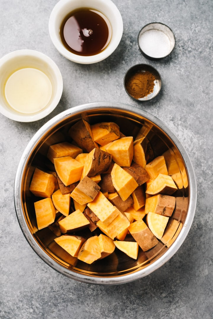 The ingredients for roasted sweet potato cubes with cinnamon and maple syrup arranged on a concrete background.