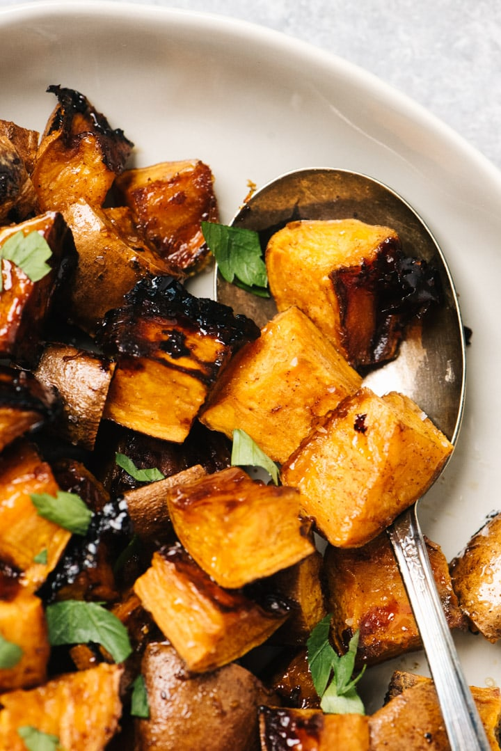 Cinnamon roasted sweet potatoes in a serving bowl with a vintage spoon, garnished with parsley.
