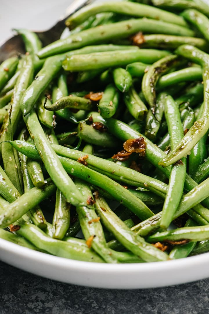 Side view, green beans sautéed with garlic in a white serving bowl.