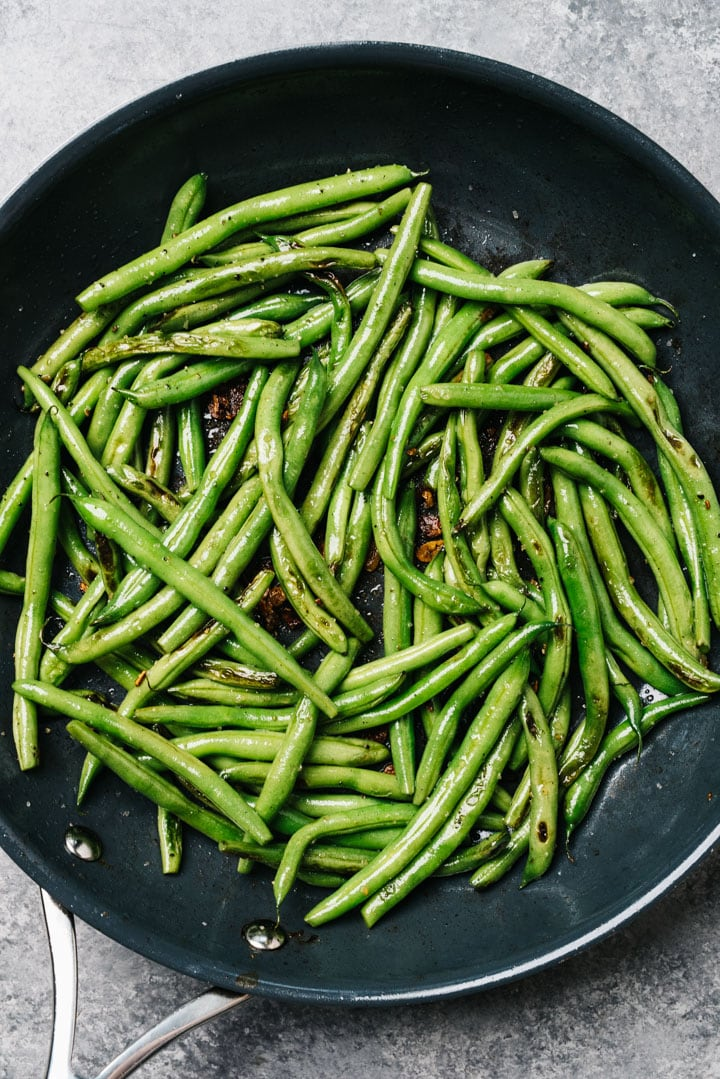Sautéed garlic green beans in a skillet seasoned with salt and pepper.