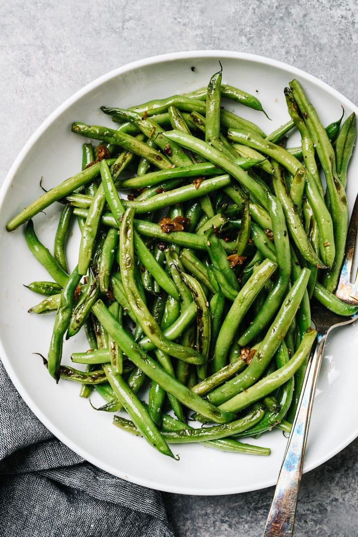 A bowl of sautéed garlic green beans with a silver serving fork and dark grey linen napkin.