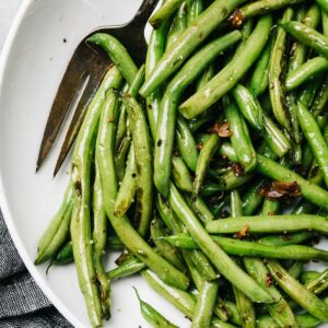 Garlic green beans in a white serving bowl with a vintage serving fork and a dark grey linen napkin.